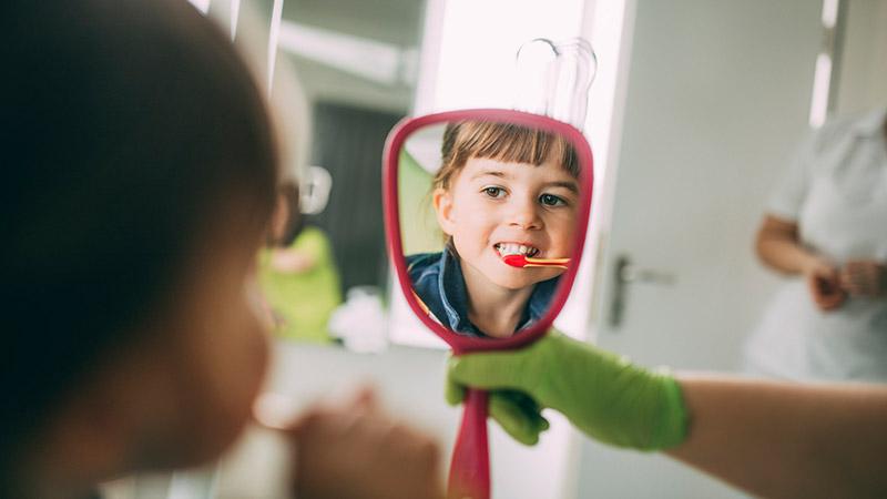 Junges Mädchen putzt sich beim Kinderzahnarzt in Magdeburg die Zähne.