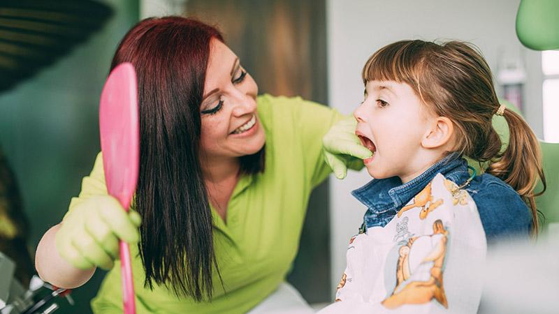 Mitarbeiterin kontrolliert Zähne eines Kindes beim Kinderzahnarzt in Magdeburg.