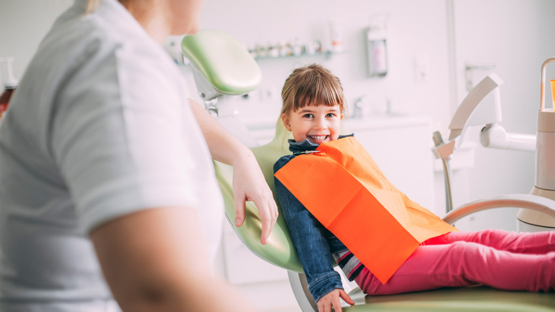 Mädchen lacht mit gesunden Zähnen beim Kinderzahnarzt in Magdeburg.