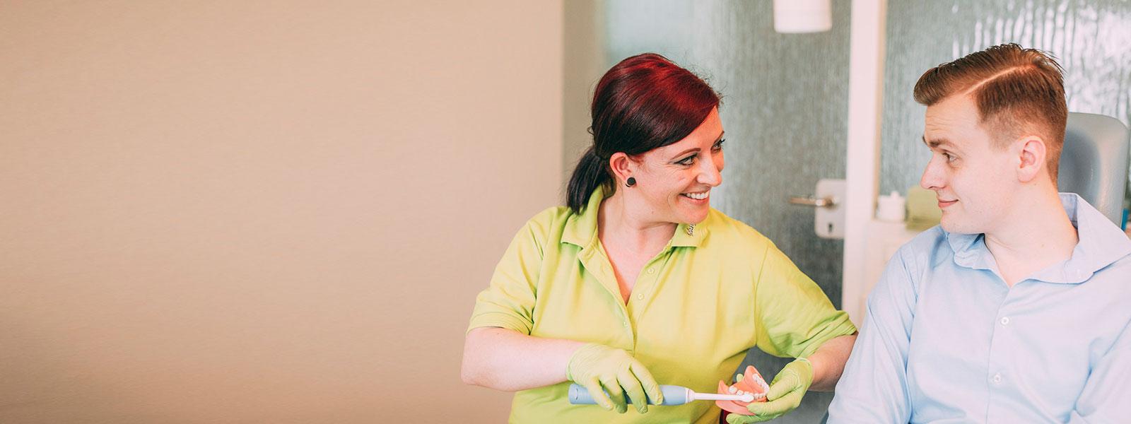 Mitarbeiterin zeigt Patient, wie er sich für Zahnprophylaxe in Magdeburg richtig die Zähne putzt.
