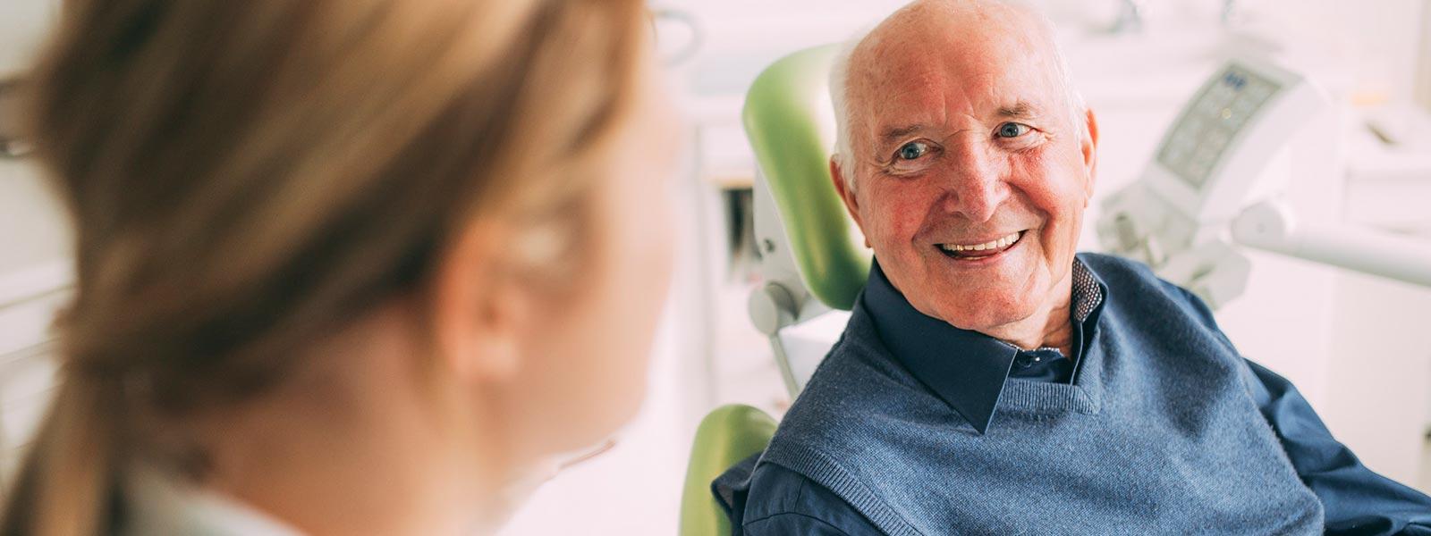 Patient lacht glücklich über Zahnerhalt in Magdeburg.